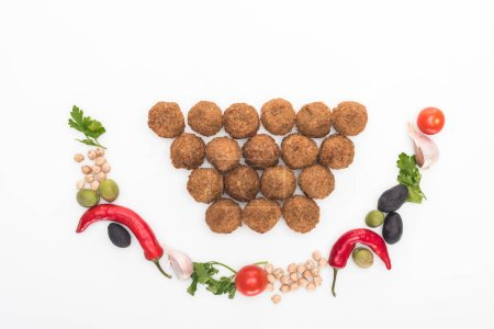 Photo for Top view of chickpea, garlic, cherry tomatoes, parsley, olives, chili pepper, green onion arranged in smile near falafel balls on white background - Royalty Free Image