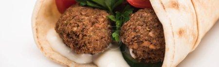 vue rapprochée des falafels frais en pita avec légumes et sauce sur fond blanc, panoramique