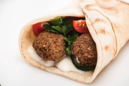 Photo for Close up view of fresh falafel balls in pita with vegetables and sauce on white background - Royalty Free Image