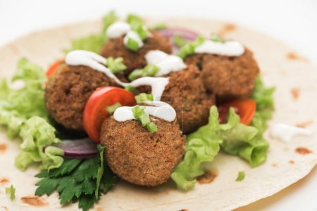 Photo for Close up view of fresh falafel balls on pita with vegetables and sauce on white background - Royalty Free Image