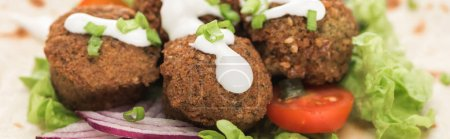 Photo for Close up view of fresh falafel balls on pita with vegetables and sauce, panoramic shot - Royalty Free Image