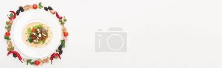 Photo pour Vue du dessus des légumes disposés en rond autour du faucon pita sur assiette sur fond blanc, plan panoramique - image libre de droit