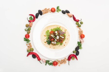 Photo for Top view of vegetables arranged in round frame around falafel on pita on plate on white background - Royalty Free Image
