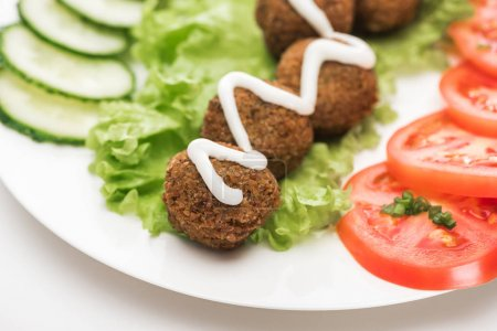 Photo for Close up view of falafel with sauce on plate with sliced vegetables on white background - Royalty Free Image