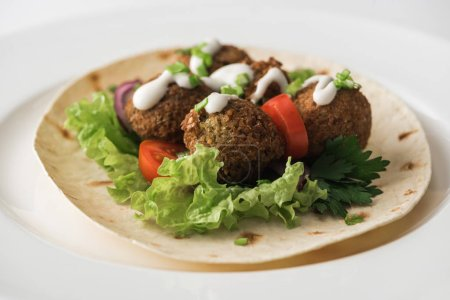 Photo for Close up view of falafel with sauce on pita with vegetables in white plate - Royalty Free Image