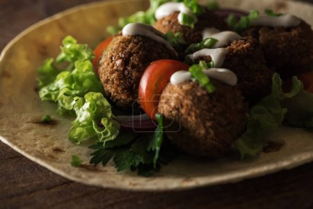 Photo for Close up view of falafel with sauce on pita with vegetables in darkness - Royalty Free Image