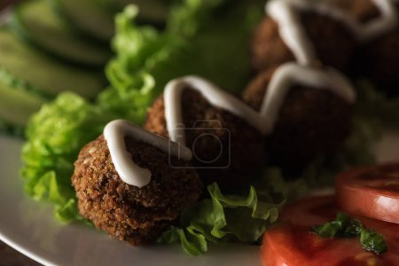 close up view of falafel with sauce on plate with sliced vegetables in dark