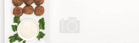 Photo pour Vue du dessus des boules de falafel sur assiette avec sauce et persil sur fond blanc, panoramique - image libre de droit