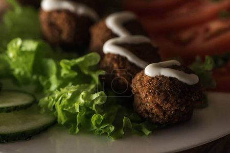 close up view of falafel with sauce on plate with sliced vegetables in dark, panoramic shot
