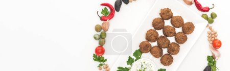 Photo for Top view of vegetables arranged in round frame around falafel on plate with sauce on white background, panoramic shot - Royalty Free Image