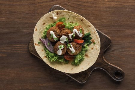 Photo for Top view of falafel with vegetables and sauce on pita on wooden table - Royalty Free Image