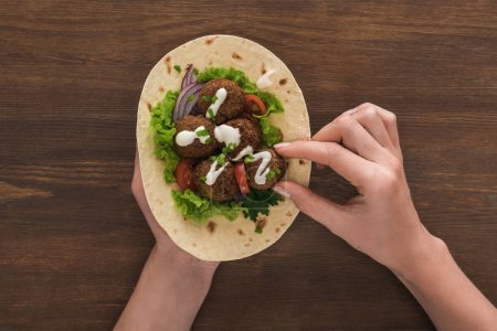 Photo for Cropped view of woman eating falafel with vegetables and sauce on pita on wooden table - Royalty Free Image