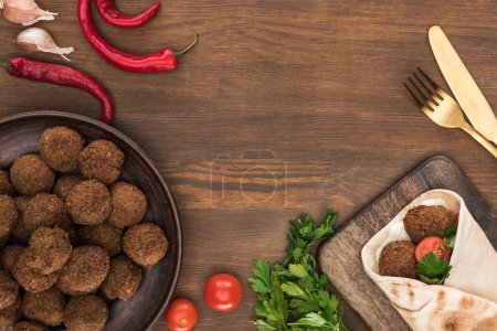 top view of falafel with vegetables and sauce in pita near balls, parsley, tomatoes, chili pepper, garlic and cutlery on wooden table