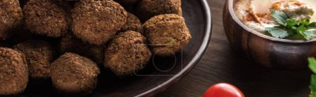 Photo for Close up view of falafel balls near hummus on wooden table, panoramic shot - Royalty Free Image