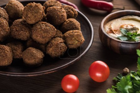 close up view of falafel balls near hummus on wooden table