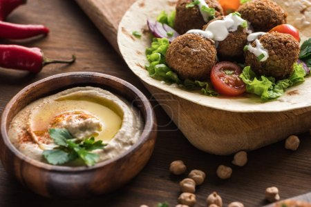 Photo for Close up view of falafel with vegetables and sauce on pita near hummus on wooden table - Royalty Free Image