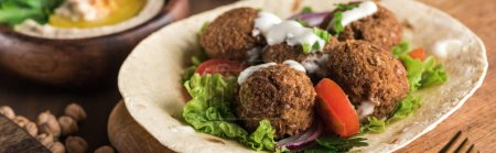 Photo for Close up view of falafel on pita with vegetables and sauce near hummus on wooden table, panoramic shot - Royalty Free Image