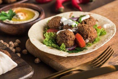 Photo pour Vue de près du falafel sur pita avec légumes et sauce près de l'hummus sur table en bois - image libre de droit