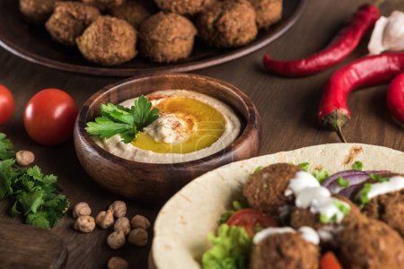 Photo for Close up view of falafel with vegetables and sauce on pita near fresh hummus on wooden table - Royalty Free Image