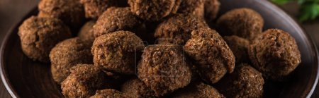 close up view of fresh cooked falafel balls on wooden table, panoramic shot
