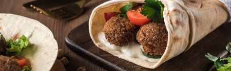 Photo for Close up view of falafel with vegetables and sauce on pita on wooden table, panoramic shot - Royalty Free Image