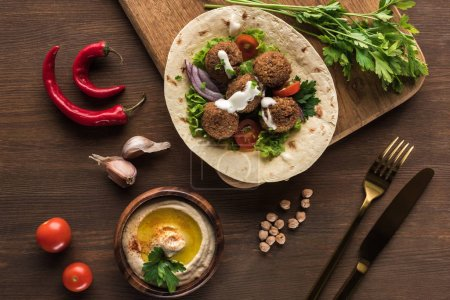 Photo pour Top view of falafel with vegetables on pita near cutlery, spices and hummus on wooden table near spices. - image libre de droit