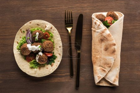 Photo for Top view of falafel with vegetables and sauce wrapped and unwrapped in pita on wooden table with cutlery - Royalty Free Image