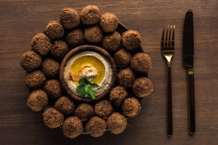 top view of falafel balls with hummus on plate near cutlery on wooden table