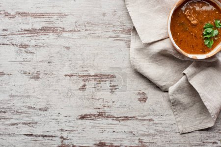 Photo pour Vue en haut de la soupe traditionnelle géorgienne kharcho avec coriandre sur nappe sur table en bois - image libre de droit