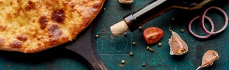 Photo for Imereti khachapuri with wine bottle and vegetables on textured green background, panoramic shot - Royalty Free Image
