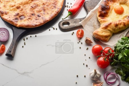 Imereti and adjarian khachapuri with vegetables and cilantro on marble texture