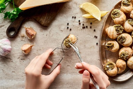 cropped view of woman eating escargots with tweezers near lemon slices, Parmesan, garlic, parsley, black peppercorn on stone background