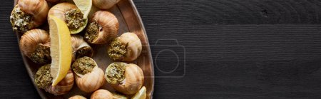 Photo for Top view of delicious cooked escargots with lemon on black wooden table, panoramic shot - Royalty Free Image