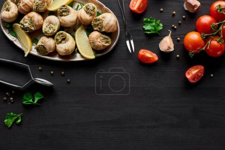 Photo for Top view of delicious cooked escargots on black wooden table with ingredients - Royalty Free Image