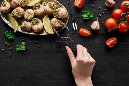 Photo for Cropped view of woman eating delicious escargots with lemon on black wooden table - Royalty Free Image