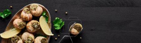 Photo pour Vue de dessus de délicieux escargots cuits au citron et pince à épiler sur table en bois noir, vue panoramique - image libre de droit