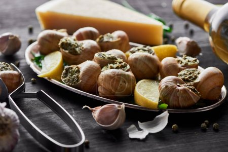 Photo for Delicious cooked escargots with lemon slices on black wooden table with spices and white wine - Royalty Free Image