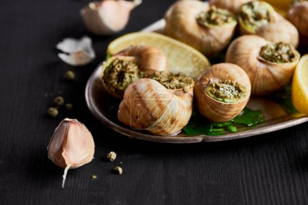 Photo for Close up view of delicious cooked escargots with lemon slices and garlic - Royalty Free Image