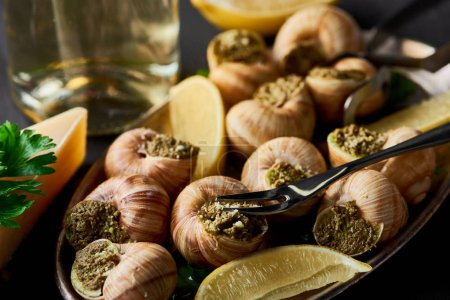 Photo for Selective focus of delicious cooked escargots with lemon, parmesan, cutlery, parsley and white wine on black wooden table - Royalty Free Image