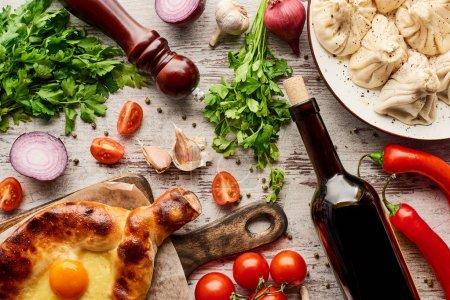 Photo pour Vue de dessus de délicieux khachapuri adjariens et khinkali près de la bouteille de vin, légumes et épices sur la table en bois - image libre de droit