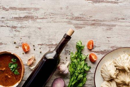 Photo pour Vue de dessus de délicieux khinkali près de la bouteille de vin, kharcho, légumes et épices sur table en bois - image libre de droit