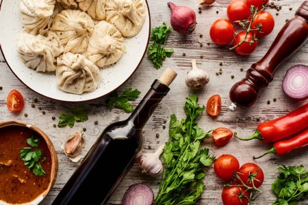 Photo for Top view of delicious khinkali near bottle of wine, kharcho, vegetables and spices on wooden table - Royalty Free Image