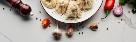 Photo for Top view of delicious khinkali near vegetables and spices on marble table, panoramic shot - Royalty Free Image