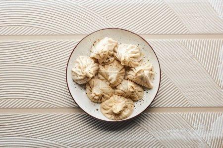 Photo pour Vue de dessus de délicieux khinkali frais sur fond beige texturé - image libre de droit