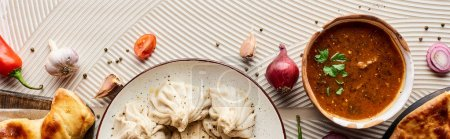 Photo for Top view of delicious khinkali, kharcho and khachapuri near vegetables and spices on beige textured background, panoramic shot - Royalty Free Image