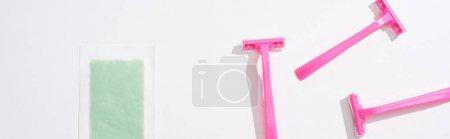 Photo pour Vue de dessus des rasoirs roses femelles et bande d'épilation sur fond blanc, vue panoramique - image libre de droit