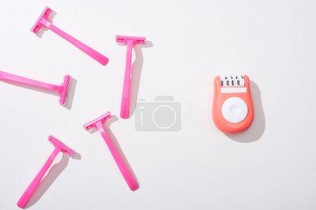 Photo pour Vue de dessus des rasoirs roses femelles et de l'épilateur sur fond blanc - image libre de droit