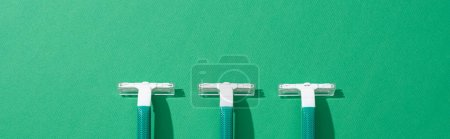 flat lay with green disposable razors on green background, panoramic shot