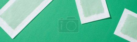 Photo pour Vue de dessus des bandes de cire d'épilation sur fond vert, vue panoramique - image libre de droit