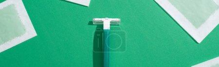 Photo pour Vue de dessus du rasoir jetable vert et des rayures de cire d'épilation sur fond vert, vue panoramique - image libre de droit